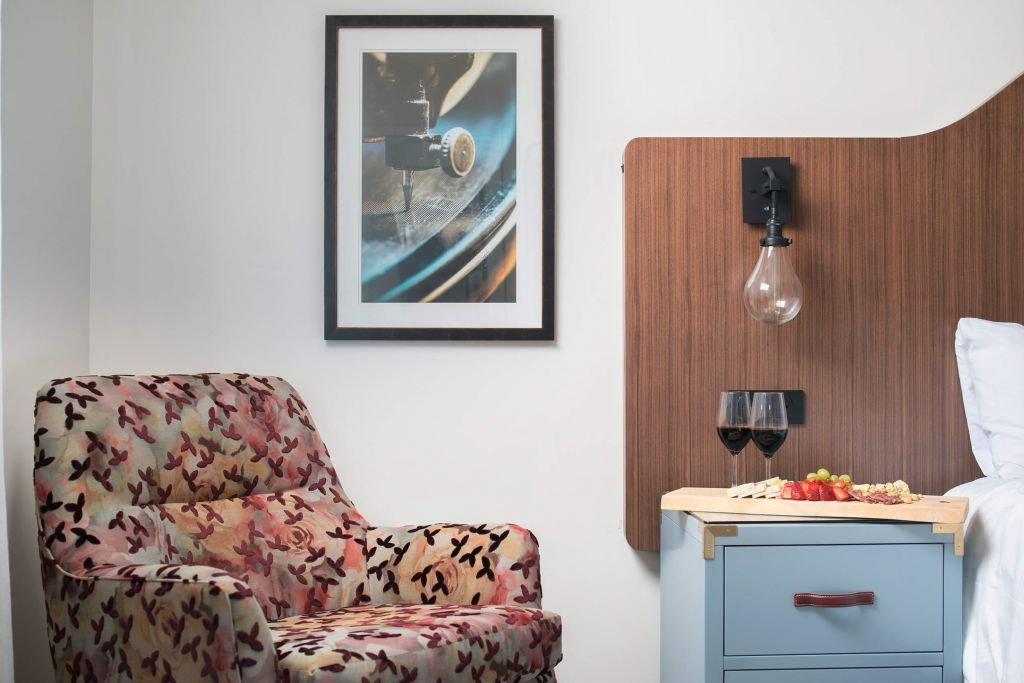 An armchair in a suite at the Fenway Hotel next to a charcuterie board and red wine.