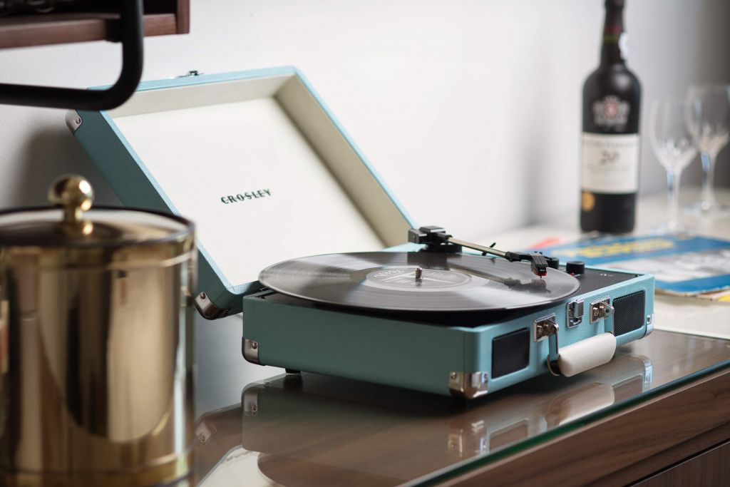 A teal-colored Crosley turntable on a wood dresser, next to a gold ice bucket.